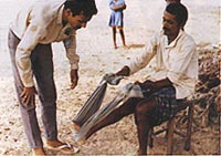 A paramedic (l) from Maitri Leprosy Centre, India, giving physical therapy to a patient (r).